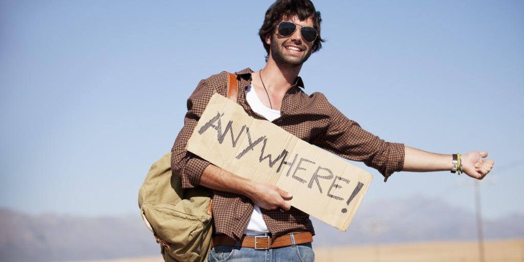 Smiling man holding Anywhere sign and hitchhiking at roadside